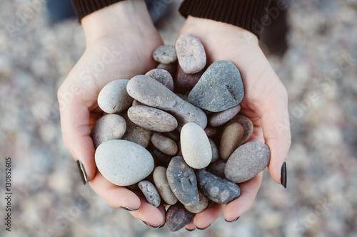 Woman holding smooth pebbles on rocky beach Fototapeta