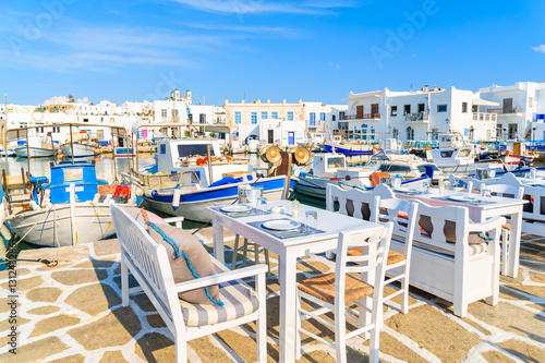 Платно Greek taverna tables and fishing boats anchoring in Naoussa port, Paros island,