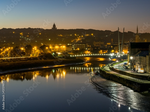 Fotografia Lancaster City at dawn over River Lune with sunrise glow and street lights spark