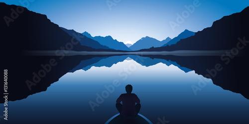 Obraz na plátně Un homme zen, assis à l'avant d'une barque, médite en contemplant le paysage calme et magnifique d'un lac entouré de montagnes