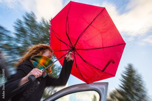 an einem stürmischen Tag versucht eine Frau einen Regenschirm aufzuspannen Fototapeta