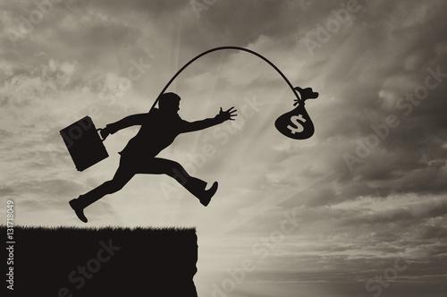 Obraz na plátne Man running for bag full of money into abyss