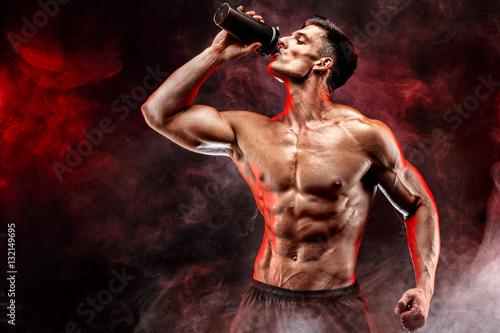 Obraz na plátně Muscular man with protein drink in shaker over dark smoke background