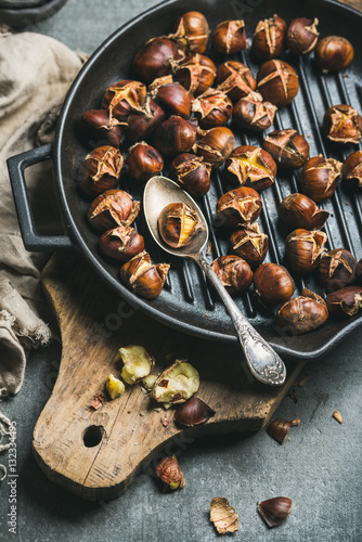 Roasted chestnuts in cast iron grilling pan over rustic wooden board and grey concrete stone background, selective focus, vertical composition