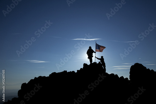 Obraz na płótnie Two soldiers raise the American flag on top of the mountain