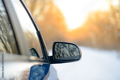 Stampa su Tela Close up Image of Side Rear-view Mirror on a Car in the Winter Landscape with Ev