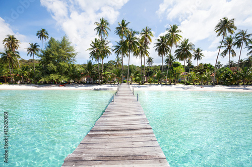 Fotografia paradise beach with turquoise water, wooden pier and tropical palm trees, summer
