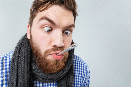 Photo Funny bearded man in scarf with thermometer at his mouth