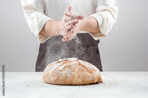 Photographie The male hands in flour and rustic organic loaf of bread