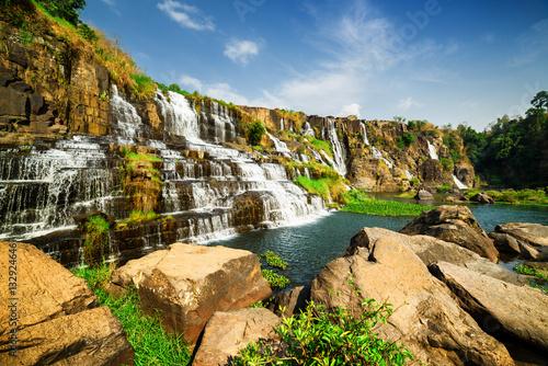 Fototapeta Niesamowity widok na naturalny kaskadowy wodospad z krystaliczną wodą