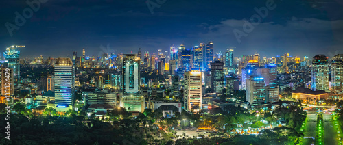 Beautiful skyline panorama of Jakarta city, Indonesia showing skyscraper buildings from top, aerial view at night.