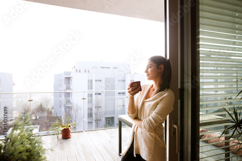 Carta da parati Woman relaxing on balcony holding cup of coffee or tea