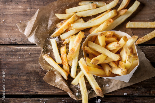 Fotografia Fast food french fries potatoes with skin served with salt and herbs in lunch box on baking paper over old dark wooden background