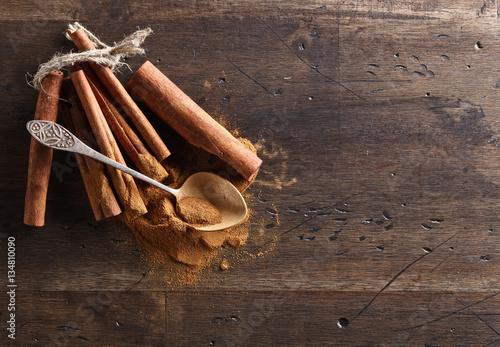 Obraz na płótnie cinnamon sticks and powder on a wooden table