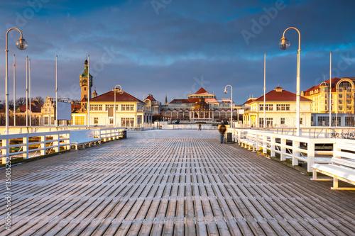 Fototapeta premium Zimny poranek, molo w Sopocie o wschodzie słońca z niesamowitym kolorowym niebem. Zima w Polsce.