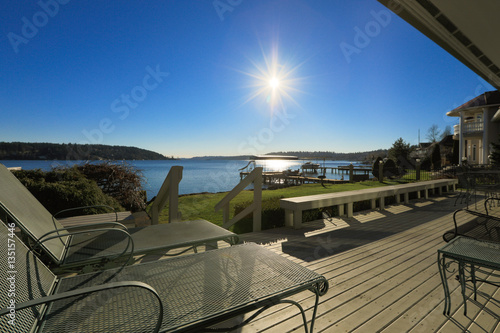 Photo Large spacious deck of grey waterfront home at sunset