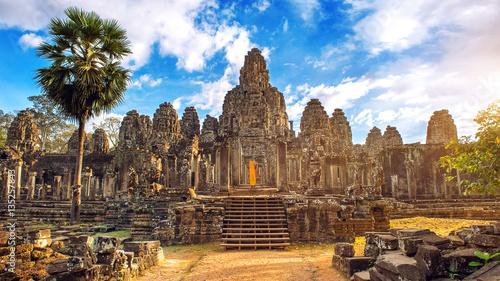 Fototapeta premium Starożytne kamienne twarze o zachodzie słońca świątyni Bayon, Angkor Wat, Siem Reap, Kambodża.