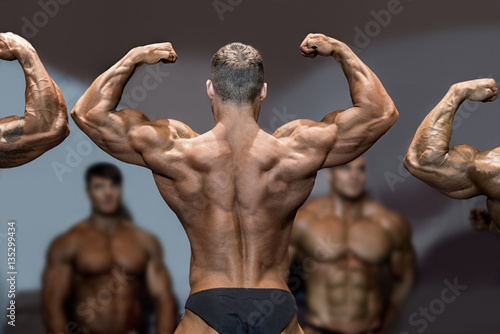 Canvas Print Bodybuilder flexing back and biceps