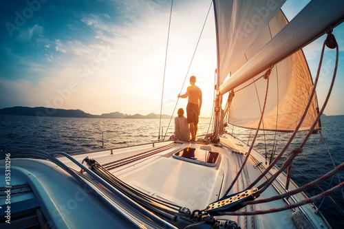 Photo Couple enjoying sunset from the deck of the sailing boat moving in a sea