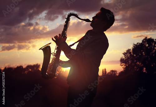 Stampa su Tela Saxophonist playing sax against sunset