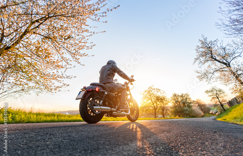 Back view of motorcycle driver on road