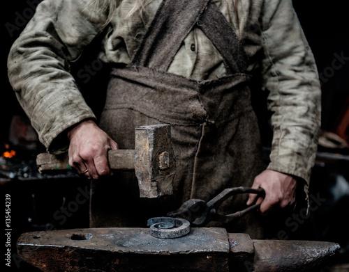 Fotografia Rustykalny kowal wykuwa przedmiot na kowadle