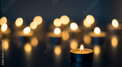 Fotografie, Obraz Flame of many candles burning on the background blue color