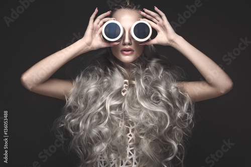 Fototapeta Beautiful girl in art dress and avant-garde hairstyles with cosmetic products in her hands