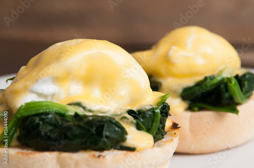 Photo Eggs benedict or eggs florentine on a white plate in the cafe