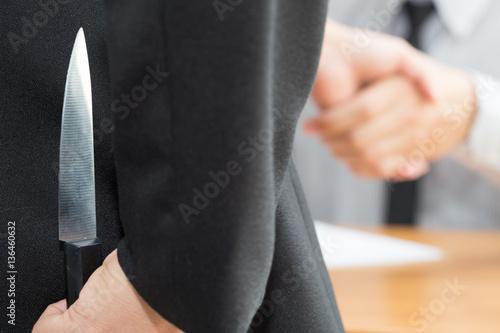 Treachery, two business making handshake a deal but hiding knive Fototapeta
