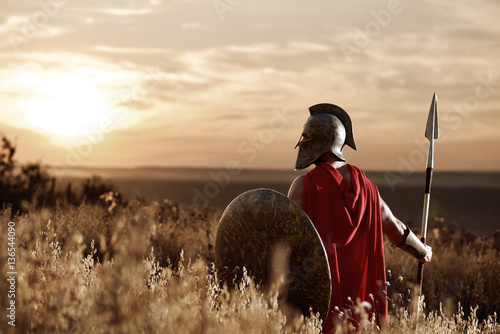 Obraz na płótnie Warrior wearing iron helmet and red cloak.