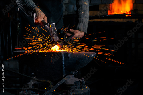 Fotografia The blacksmith manually forging the molten metal on the anvil in smithy with spa