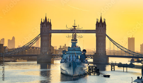 Canvas Print HMS Belfast moored in front of Tower Bridge on the River Thames at sunrise