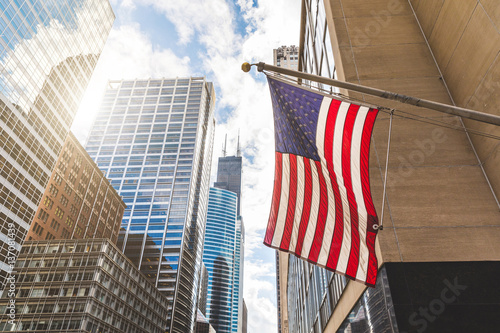 USA flag in Chicago with with skyscrapers on background