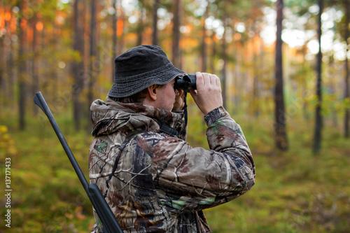 Fotografia, Obraz Hunter observing forest with binoculars
