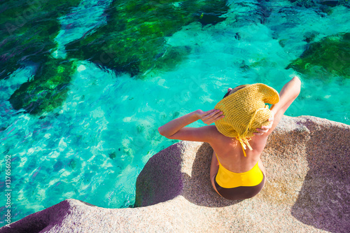 Fotografia beautiful woman in sun hat and swimsuit relaxing on the rocks over the sea
