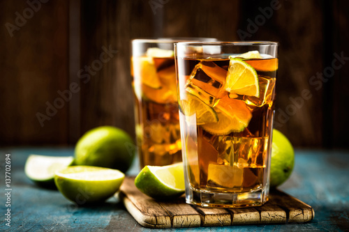 Fototapeta Cuba Libre or long island iced tea cocktail with strong drinks, cola, lime and i