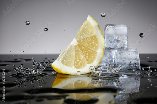 Lemon with water drops and ice cubes
