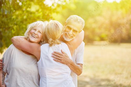 Fototapeta Lachende Senioren begrüßen sich im Sommer