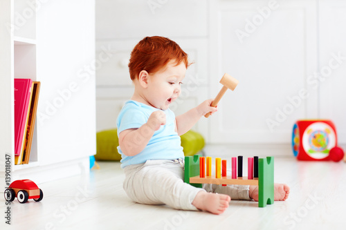 Obraz na płótnie cute infant baby playing with wooden hammer block toy