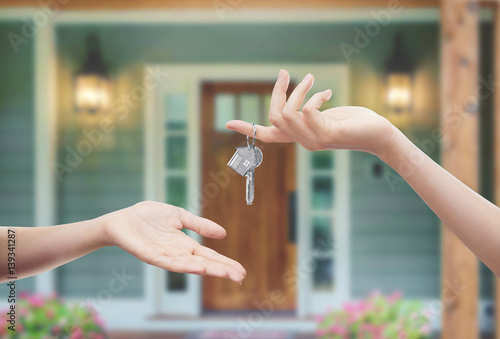 Mani con chiavi con sfondo porta di casa