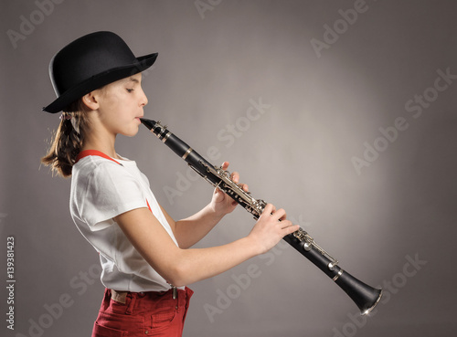 Photographie little girl playing clarinet on a gray background