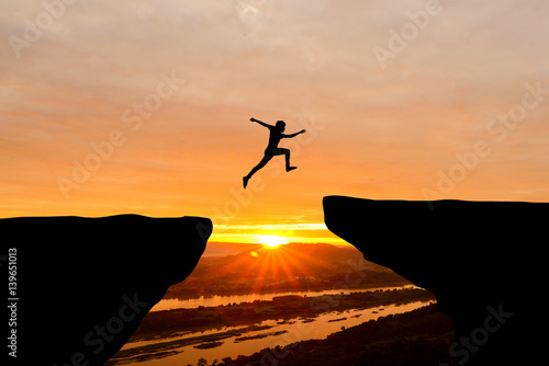 Fotomural Courage man jumping over cliff on sunset background,Business concept idea