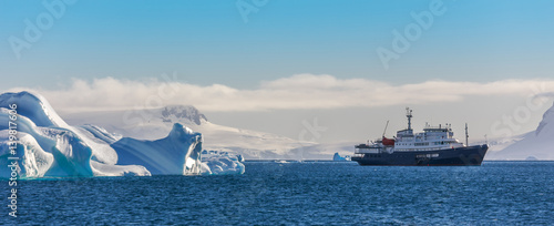 Photo Blue cruise vessel among the icebergs with glacier in background, South Shetland