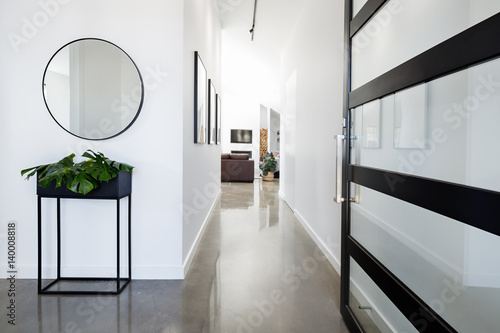 Fotografering Contemporary home entry with polished concrete floors
