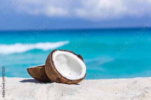 Tablou Canvas Broken brown coconut on sandy beach