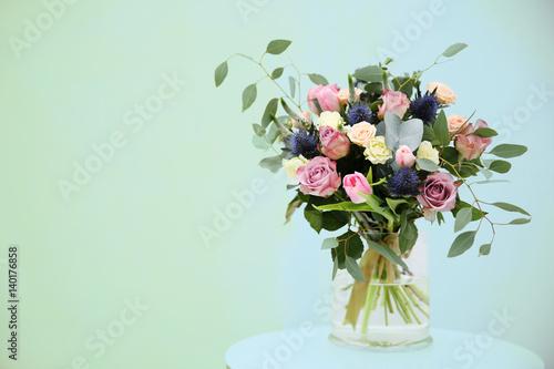 Obraz na plátne Glass vase with beautiful bouquet on light background