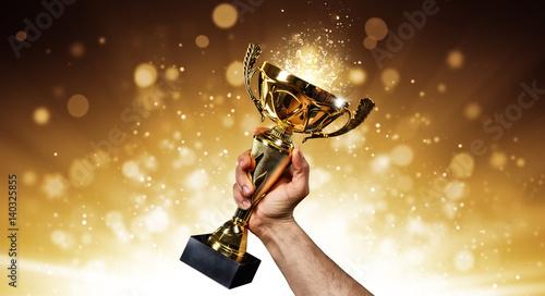 Fotografia Man holding up a gold trophy cup