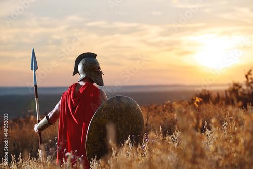 Fotografia Incognito warrior in iron helmet and red cloak.