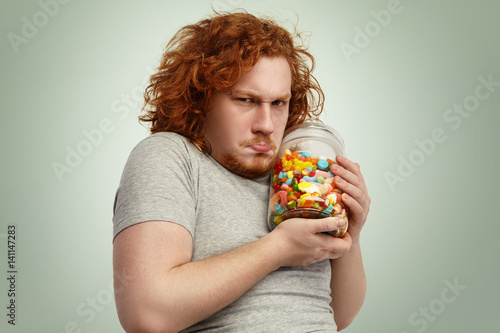 Fotografia, Obraz Obese chubby European man with ginger curly hair holding jar of sweets tight, having greedy look, frowning and grimacing, posing indoors at studio wall